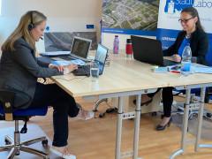 2 Frauen sitzen sich gegenüber an 2 Schreibtischen vor dem Computer und sind in ihre Arbeit vertieft.und
