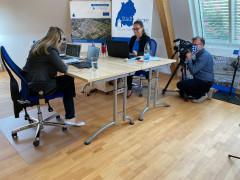 2 Frauen sitzen an ihrem Schreibtisch vor dem Computer und werden bei ihrer Arbeit gefilmt.
