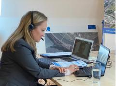 Die Moderatorin sitzt mit Headset an ihrem Computer.