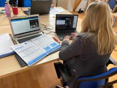 Ina Mohr sitzt mit dem Rücken zur Kamera am Schreibtisch vor 2 Laptops, ausgebreitete Dokumente liegen vor ihr.