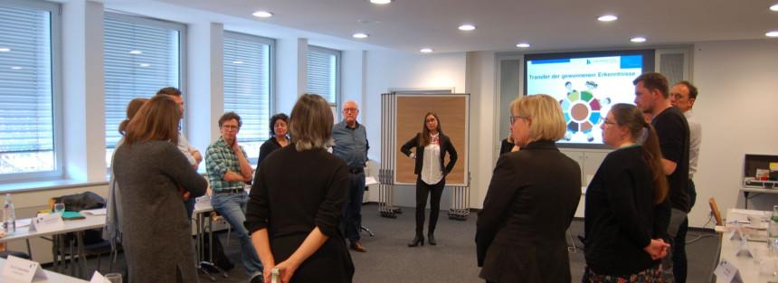 Die Workshop-Teilnehmenden stehen in einer Diskussionsrunde kreisförmig beisammen.